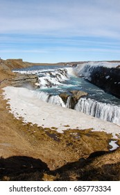 Gullfoss waterfall, popular destination of golden circle route in southwest Iceland, with foreground of snow on dry grass on sunny day with white cloud on blue sky, rainbow above the turquoise water