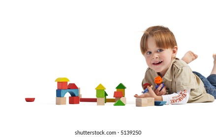 Gulliver in the Country of Lilliputs. Cute 3-years old boy and small town build from wooden blocks. Isolated on white background.