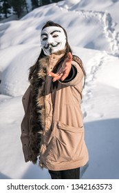Gulmarg, Kashmir, Date- 10 March, 2019- Portrait of a female belonging to the Anonymous group wearing a Vendetta mask outdoors in the snow with a brown jacket