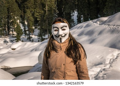 Gulmarg, Kashmir, Date- 10 March, 2019- A girl belonging to the Anonymous group wearing a Vendetta mask outdoors in the snow with a brown jacket