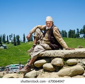 Gulmarg, Kashmir, India - Circa June 2014 - A shot of a Kashmiri man in traditional attire sitting on a rock in Gulmarg, Kashmir, India