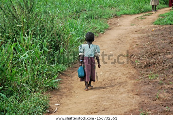 GULU, UGANDA, AFRICA - CIRCA MAY 2005:  Unidentified little girl carries a blue jerry-can down a dirt path circa May 2005 in Uganda, Africa.