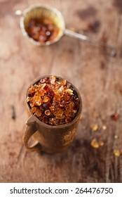 Gum arabic, also known as acacia gum - in wooden mug