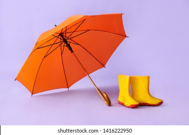 Gumboots and umbrella on color background