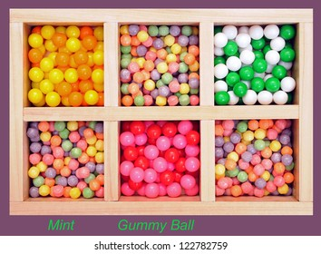 gummy ball and multicolor mint candies in wooden box