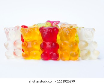 Gummy bears candy in a row on white isolated background.