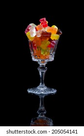 Gummy bears in a glass on a black background.