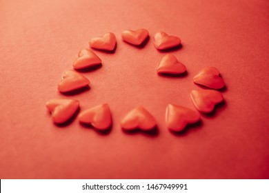 A lot of gummy hearts making the shape of a giant heart in red with red background