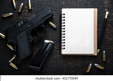 Gun and ammunition and blank notebook on dark wooden table. top view