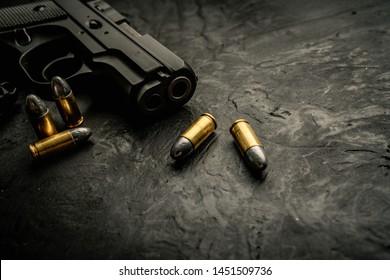 Gun with ammunition on black background. top view