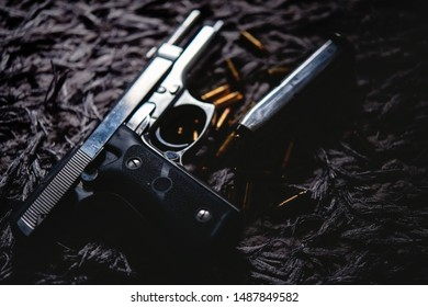 Gun with ammunition on carpet background.