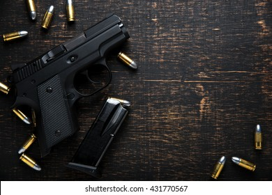 Waffe und Munition auf dunklem Holztisch. Draufsicht