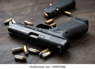 Waffe mit Munition auf Holzhintergrund.