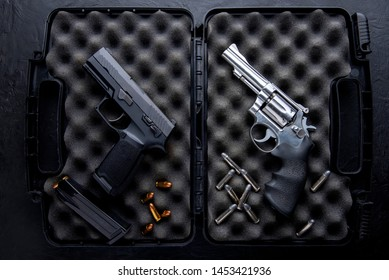 Gun with ammunition in open case for gun on dark table. Top view