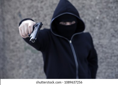 gun armed l terrorist in a mask with a hood
