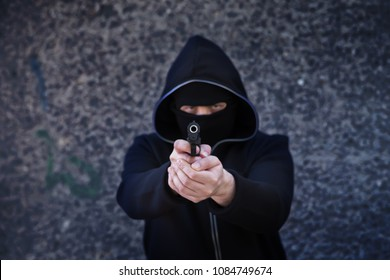 gun armed man in a mask with a hood