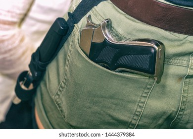 Gun in the back pocket of greenish trousers
