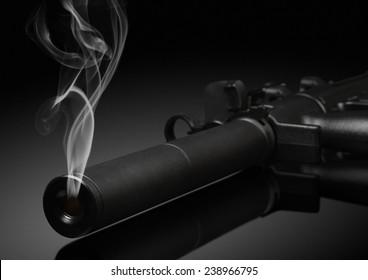 gun barrel with smoke on black background. Soft focus