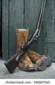 gun and boots before old wooden background