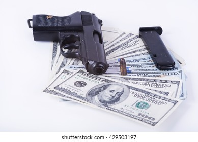 Gun with bullet on US dollar banknotes, crime and corruption.