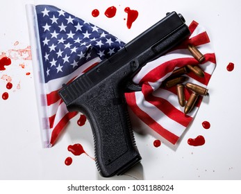 Gun with bullets, on an American flag and drops of blood