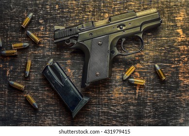 gun with bullets on wooden background