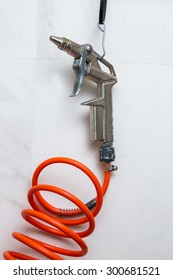 gun for compressed air with wire hooked to a nail