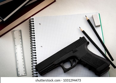 Gun control legislation and school shooting prevention concept with a gun on a notebook surrounded by school supplies and copy space