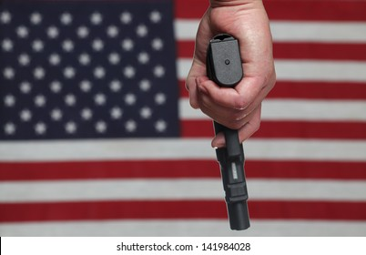 Gun Control USA Style/Hand holding automatic pistol over slightly blurred background of US Flag