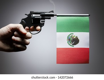 Gun crime concept of hand pistol showing the flag of mexico