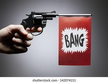 Gun crime concept of hand pistol showing a bang flag