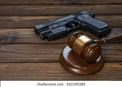 A gun and a hammer judge on the background of a wood texture table. idea: Do not legally wear and purchase weapons. weapon crime. court, law.