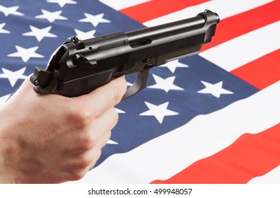 Gun in hand with flag on background - USA