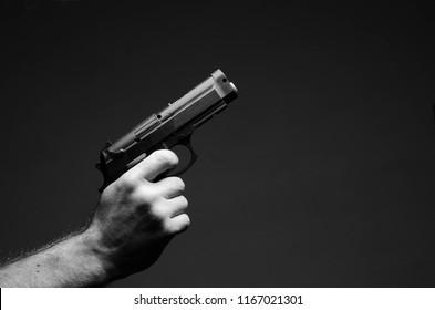 gun in hand, on a dark background