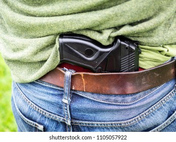 gun is hidden behind the back of a man's belt