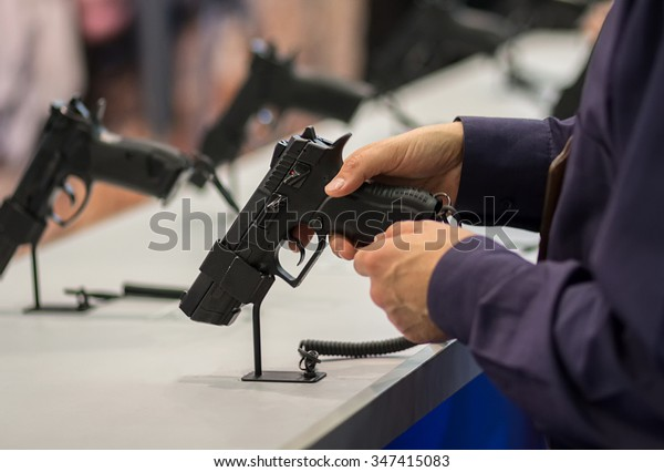 Gun in his hand. Exhibition and sale of weapons