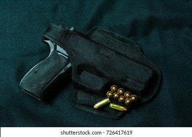 A Gun in holster gun and bullet on black background.
