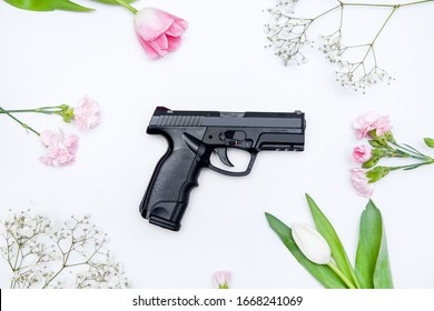 The gun lies on a background of flowers. Romantic composition of weapons