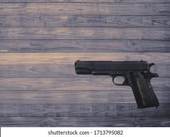 The gun lies on a wooden surface. Background texture.