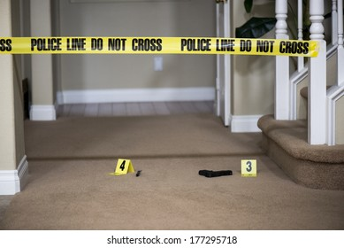 a gun lying on the ground next to a crime scene marker.