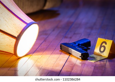 A gun is marked with an evidence marker on the floor of a home. A knocked over lamp lays nearby.