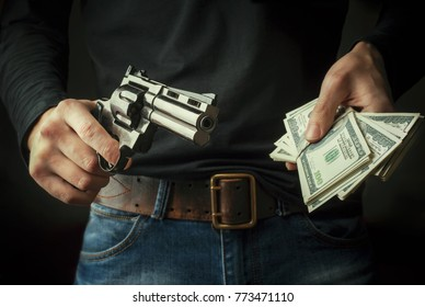 Gun and money in a hands. Bank robbery