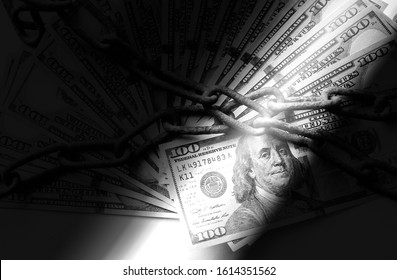 Gun and money in old rusty chains. Arrested for illegal crime. Broken the law. Bribe concept. Light beam. Black and white.