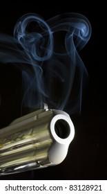 gun moving and belching smoke as a bullet leaves