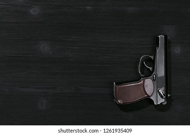 Gun on black wooden table background with copy space.