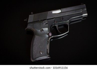 The gun on the glass surface.Hand gun on glass background.Weapon