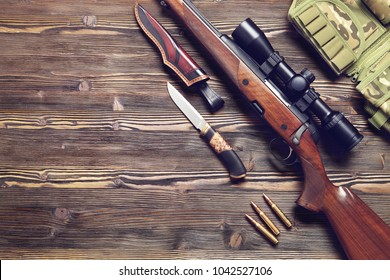 A gun with an optical sight, a hunting knife on a wooden background.Top view.