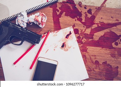 gun over white paper sheet and pencils, books with red flesh blood, smartphone   and crumpled paper ball on  tile  floor, committed suicide , conceptual image, Gun control concept