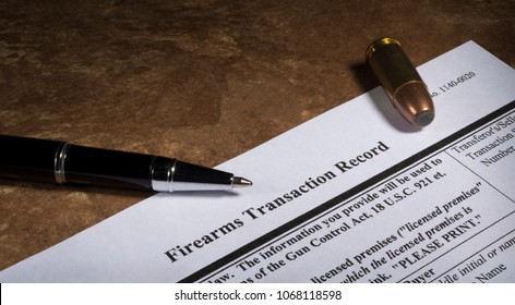 Gun paperwork for a NICS check from the FBI with a pen and cartridge