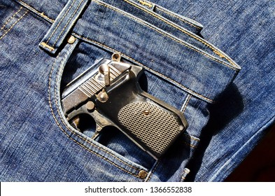 Gun in a pocket of jeans trousers fighting loaded